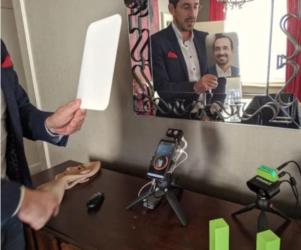 Ингмар Брудер, генеральный директор и основатель Trinamix, демонстрирует, как технология распознавания лиц компании невозможно обмануть напечатанной фотографией с высоким разрешением. [Фото: предоставлено Сетом Розенблаттом]